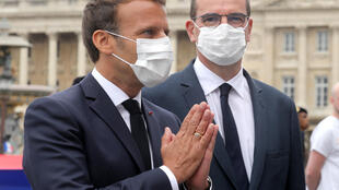 Wearing a face mask, French President Emmanuel Macron (L) greets guests flanked by Prime Minister Jean Castex at the Bastille Day military ceremony in Paris on July 14, 2020.