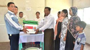 El funcionario de inmigración de Myanmar entrega el documento de identificación a una mujer rohingya no identificada, que pertenece a la familia rohingya de cinco miembros en el campamento de repatriación de la ciudad de Taungpyoletwei en Maungdaw, cerca de la frontera con Bangladesh.