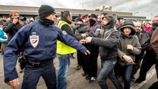 Un policier disperse des manifestants rassemblés à l'appel de Pegida à Calais le 6 février.