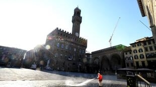 A municipal worker disinfects the Piazza della Signoria, in front of the Palazzo Vecchio, in Florence, on March, 21 2020, as part of measures taken by the Italian government to fight against the spread of the COVID-19 (novel coronavirus).