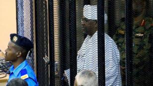 El expresidente de Sudán, Omar al- Bashir, es vigilado dentro de una jaula en el juzgado donde enfrenta cargos de corrupción, en Jartum, Sudán, el 19 de agosto de 2019.