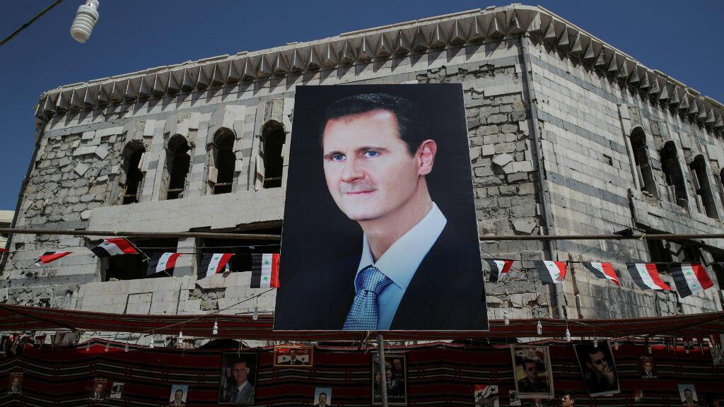 Un hombre pasa frente a una pancarta que muestra al presidente sirio Bashar al Asad en Duma, en las afueras de Damasco, Siria, el 17 de septiembre de 2018.