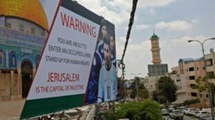 ملصق مرفوع في مدينة الخليل بالضفة الغربية يحمل صورة قبة الصخرة ولاعب كرة القدم الأرجنتيني ليونيل ميسي، ويطالبه بعدم المشاركة في المباراة الودية ضد إسرائيل، في صورة مؤرخة 5 حزيران/يونيو 2018.