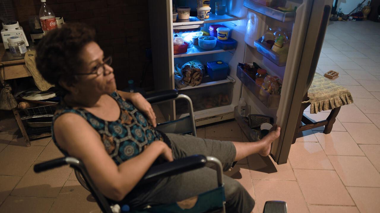 Archivo: Una residente, que permanece en una silla de ruedas debido a una pierna rota, muestra comestibles y verduras en su refrigerador, en el barrio de Petare, Caracas, el 25 de julio de 2019.