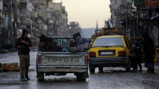 Delil Souleiman, AFP | Syrians sitting in the back of a pick-up track pass a member of Syrian Democratic Forces on a destroyed street in Raqa, the former de facto capital of the Islamic State (IS) group, on February 18, 2018.