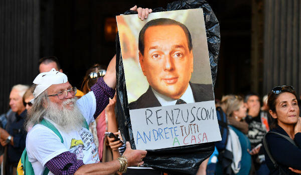 "A supporter of the Five-Star Movement holds a poster reading ""Renzusconi, you will all go home"" and showing a photomontage of former Italian premiers Silvio Berlusconi and Matteo Renzi. Photo: Alberto Pizzoli, AFP"