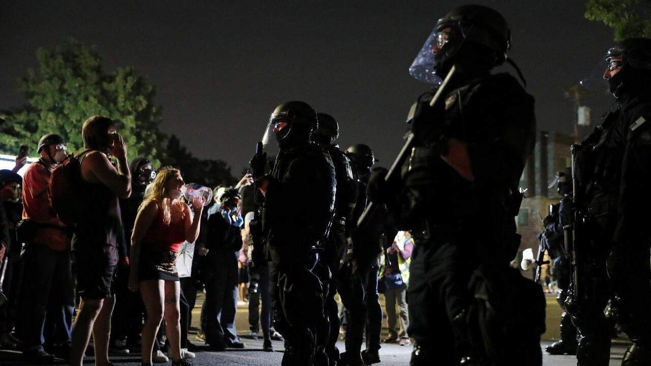 Un grupo de manifestantes frente a los oficiales antidisturbios en Portland, Oregon, en la noche del viernes 4 de septiembre de 2020.