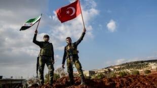 مقاتلان من المعارضة السورية التي تدعمها تركيا يرفعان علم تركيا (يمين) وعلم الجيش السوري الحر  عند حاجز في بلدة أعزاز في سوريا في الأول من شباط/فبراير 2018