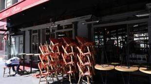 Un employé installe des tables et des chaises avant la réouverture des terrasses des cafés, bars et restaurants, le 30 mai 2020 à Paris