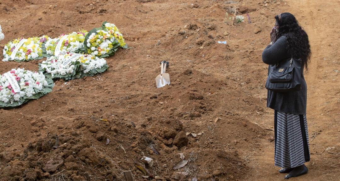 Una mujer llora a su hermano, quien murió por Covid-19 y fue enterrado en un cementerio a las afueras de Sao Paulo en Brasil, el 4 de junio de 2020.