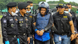 Anti-crime unit personnel escort Bangladeshi hospital owner Mohammad Shahed (C), who was arrested on suspicion of distributing fake certificates saying patients had tested negative for COVID-19