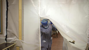 A healthcare worker walks through a sealed off Covid patient area in the ER at Oakbend Medical Center in Richmond, Texas