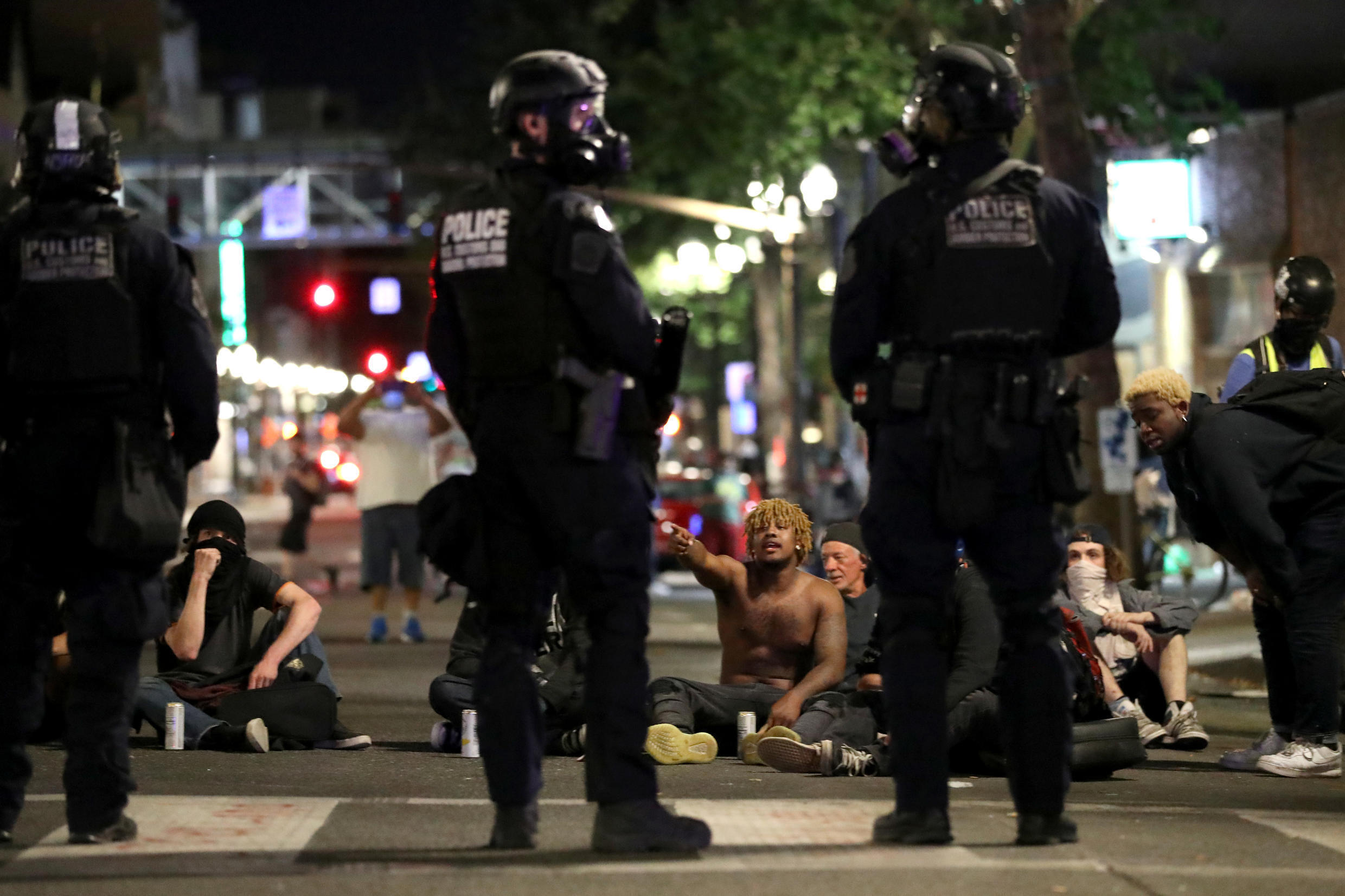 Demonstrators sit on the street during a protest against racial inequality and police violence in Portland, Oregon, U.S., July 27, 2020.