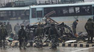 Des forces de sécurité indiennes inspectent un autobus à la suite de l'attaque d'un convoi de la police, le 14 février 2019.