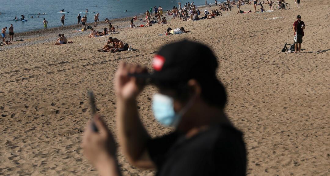 La gente disfruta del clima soleado en la playa de la Barceloneta, en medio del brote de coronavirus en Barcelona, España, el 21 de mayo de 2020.