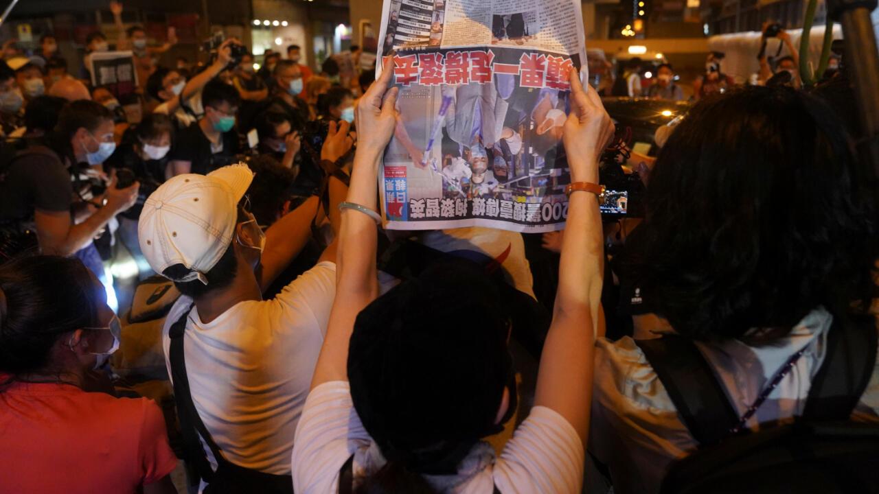 Una persona levanta el periódico Apple Daily mientras conceden la libertad bajo fianza a su fundador y propietario Jimmy Lai, en la madrugada del 12 de agosto de 2020.