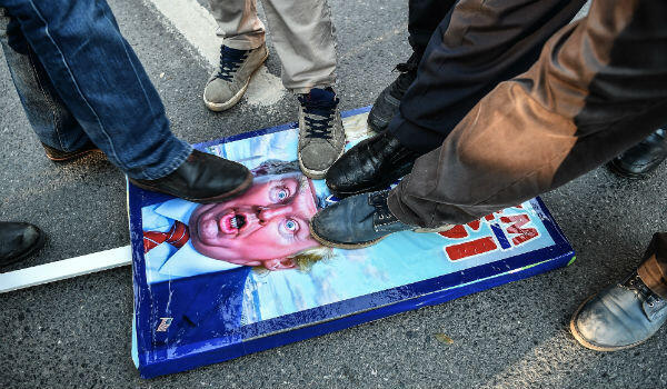 Protesters step on a poster of US President Donald Trump during a demonstration in Istanbul on December 8, 2017.