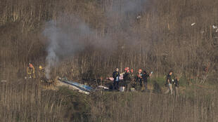 Des pompiers et enquêteurs sur les lieux du crash de l'hélicoptère transportant Kobe Bryant et sa fille Gianna, le 26 janvier 2020 à Calabasas, en Californie