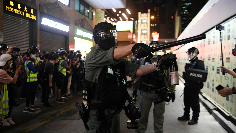 La policía de Hong Kong advierte a los periodistas que retrocedan durante una protesta en el primer aniversario de una protesta masiva contra el proyecto de Ley de Extradición, en el distrito central de la ciudad, en China, el 9 de junio de 2020.