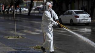 موظف في البلدية يعقم شارعا في بريشتينا بتاريخ 17 آذار/مارس 2020