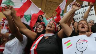 Unas manifestantes ondeando banderas libanesas y gritando lemas antigubernamentales, durante el séptimo día de protesta en el centro de Beirut, Líbano, el 23 de octubre de 2019.
