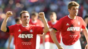 Le défenseur Philipp Lahm (à g.) et l'attaquant Thomas Müller, samedi 7 mai 2016 à Ingolstadt, célèbrent le quatrième titre consécutif de champion d'Allemagne de leur équipe, le Bayern Munich.