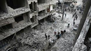 Des civils syriens inspectent les dégâts causés à Hamouria, dans la région du Ghouta orientale, après le bombardement des forces gouvernementales syriennes et de leurs alliés russes, le 6 janvier 2018.