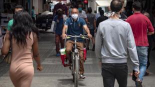 مغاربة يسيرون في احد شوارع الرباط واضعين كمامات في 25 حزيران/يونيو 2020