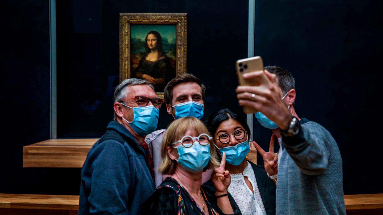 Los visitantes que usan máscaras protectoras toman fotografías frente a la pintura de Leonardo da Vinci La Gioconda (Mona Lisa), en el Museo del Louvre en París, Francia, 06 de julio de 2020. Después de un cierre de casi cuatro meses debido a la pandemia de coronavirus, el Museo del Louvre reabre al público.