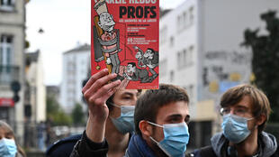 Un homme brandit un numéro de Charlie Hebdo consacré à l'enseignement sur la laïcité lors d'un rassemblement à Rennes le 17 octobre 2020 en hommage au professeur tué la veille dans les Yvelines