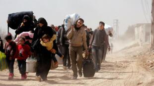 Un grupo de sirios tratando de huir de la aldea de Beit Sawa, ubicada al este de Guta, el 15 de marzo de 2018.