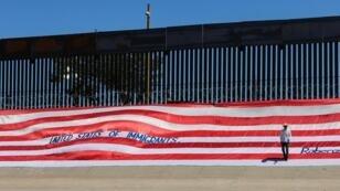 Un Mexicain plaçant un drapeau américain à la frontière entre les deux pays pour protester contre Donald Trump, le 6 juin 2019.
