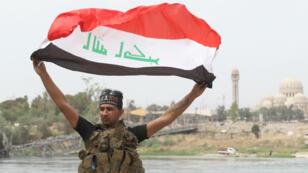Un soldat irakien parade dans le centre-ville de Mossoul, avec un drapeau irakien, le 8 juillet 2017.