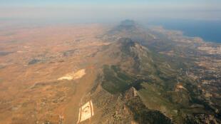 """صورة التُقطت في 14 حزيران/يونيو 2015 تُظهر سلسلة جبال تقع في الشطر الشمالي من الجزيرة حيث رُسم علم """"جمهورية شمال قبرص التركية"""" والعلم التركي"""