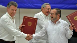 """وقع الرئيس الكولومبي خوان مانويل سانتوس والقائد الأعلى لقوات المسلحة الثورية الكولومبية """"فارك"""" تيمولين خيمينيز اتفاقا تاريخيا في كوبا 23 حزيران/يونيو 2016"""