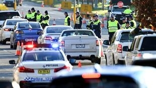 Police in the southern New South Wales border city of Albury check cars crossing from Victoria on July 8 after authorities closed the state border