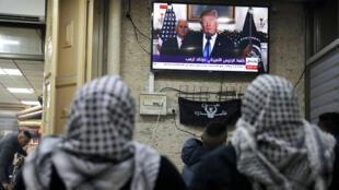 Palestinos ven una transmisión televisiva del presidente de Estados Unidos, Donald Trump, que brinda un discurso donde anunció que Estados Unidos reconoció a Jerusalén como la capital de Israel, en la Ciudad Vieja de Jerusalén el 6 de diciembre de 2017.