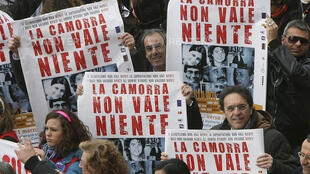 "FILE PHOTO: Demonstrators hold banners reading ""Camorra worth nothing"" as they march in the southern city of Naples March 21, 2009."