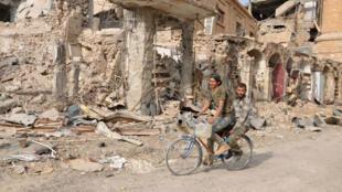 Deux hommes à vélo dans les rues de Deir Ezzor lors d'une opération menée par les forces gouvernementales syriennes contre l'EI, le 4 novembre 2017.