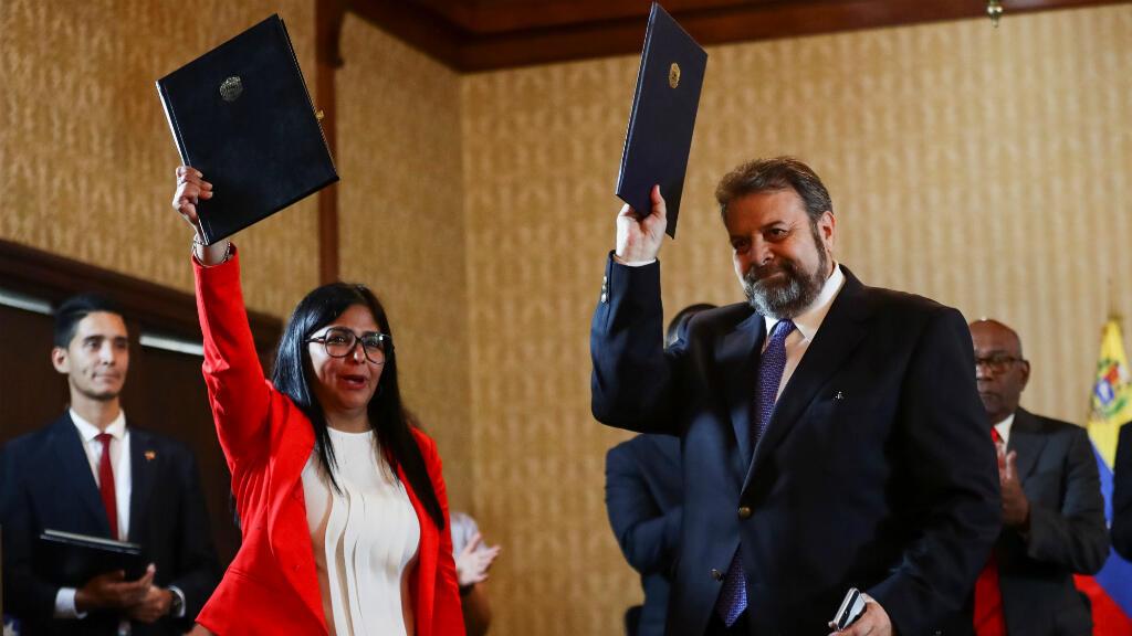 Delcy Rodríguez, vicepresidenta de Venezuela, y el diputado opositor Timoteo Zambrano participan en la firma de un acuerdo hoy, lunes durante la presentación de una mesa de diálogo nacional en Caracas, Venezuela, el 16 de septiembre de 2019.