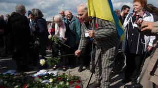 Un ancien prisonnier dépose une rose lors de la cérémonie des 70 ans de la libération du camp de Buchenwald, près de Weimar, en Allemagne.