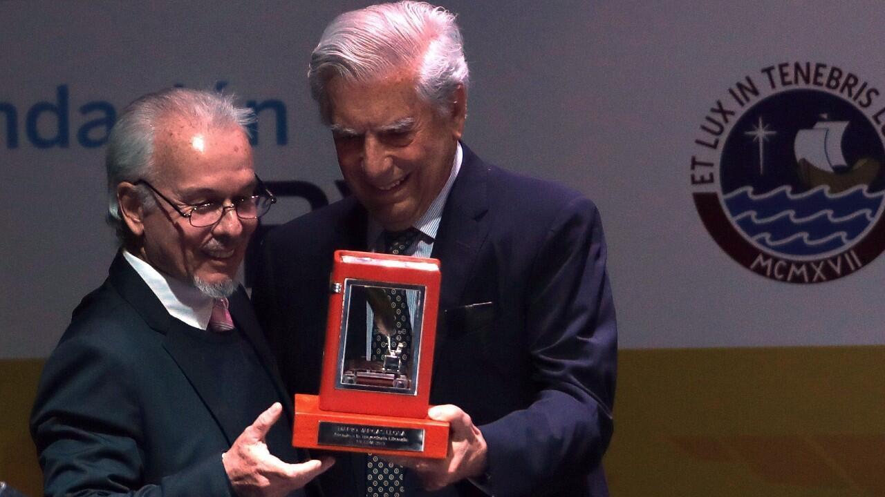 Mario Vargas Llosa recibe el premio de manos de Carlos Alvariño, presidente de la Cámara Peruana del Libro.