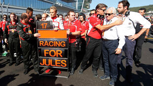 Jules Bianchi's Marussia teammates pause in his support at the Russian Grand Prix on October 12.