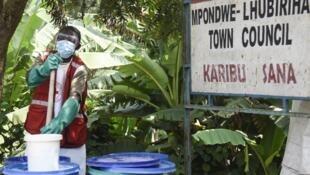 Un infirmier prépare une solution désinfectante au centre de dépistage sanitaire de Mpondwe, ville frontalière de l'Ouganda avec la République démocratique du Congo, le 13 juin 2019.