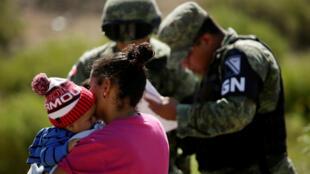 Una madre hondureña con su hijo son detenidas por miembros de la Guardia Nacional de México en Anapra, a las afueras de Ciudad Juárez, México, el 28 de junio de 2019.