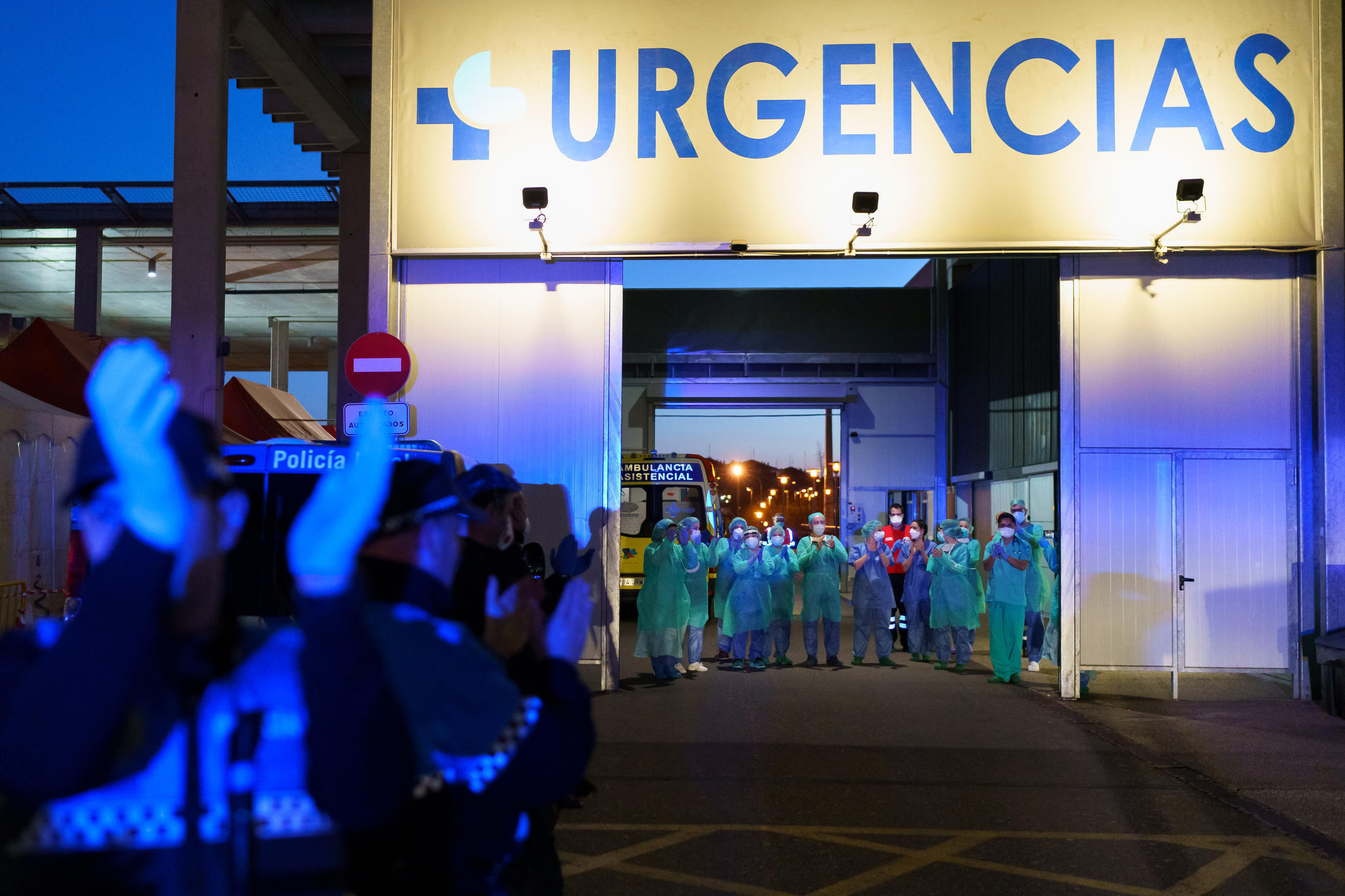 Healthcare workers dealing with the new coronavirus crisis applaud in return as they are cheered on by people outside the Burgos general hospital in Burgos, Spain on March 25, 2020.