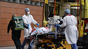 Medics take a patient from an ambulance into the Royal London hospital in London on January 19, 2021.