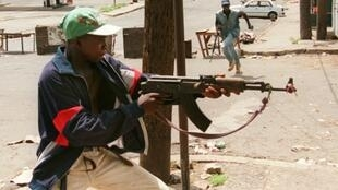 A fighter with Charles Taylor's NPFL fires at rivals from the United Liberation Movement of Liberia for Democracy (ULIMO) during Liberia's civil war in May 1996