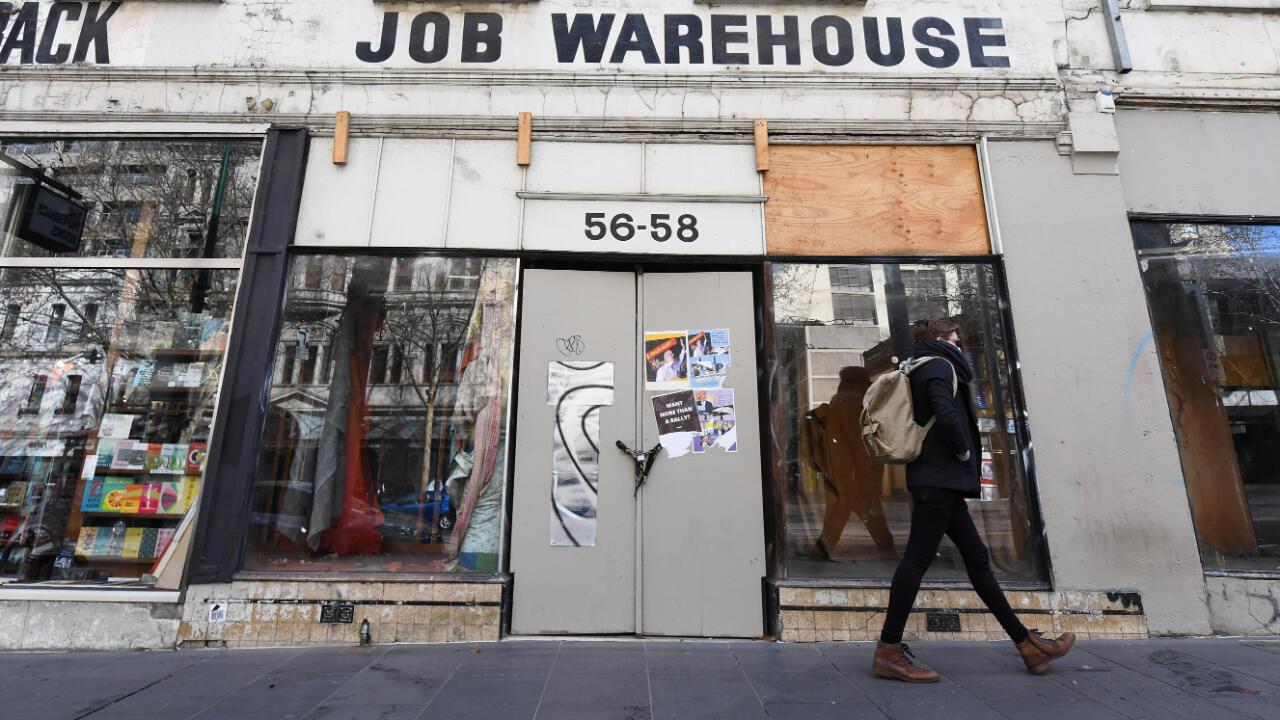 Una persona pasa frente a una tienda cerrada en Melbourne, Australia, en la víspera del inicio de una cuarentena total que se extenderá por seis semanas. 5 de agosto de 2020.