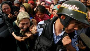 Foto de archivo de una mujer que se aferra a un policía chino cuando una multitud se enfrenta a las fuerzas de seguridad en una calle en la ciudad de Urumqi, en la Región Autónoma de Xinjiang en China, el 7 de julio de 2009.